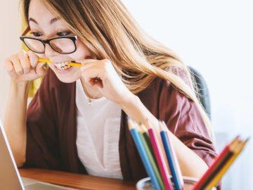 Frau vor Laptop beißt auf Stift